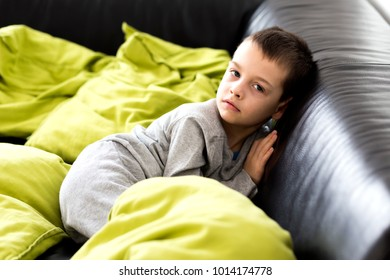 Young boy in his home relax on the couch, green pillows.