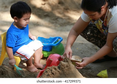 Young boy and his mother are playing with sand box on playground