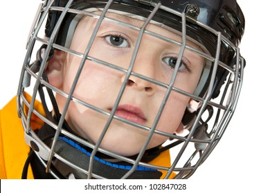 Young boy in hockey helmet with facial mask and yellow jersey. Close view on the white background