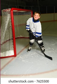 A young boy in hockey pose in front of the net of a dark arena