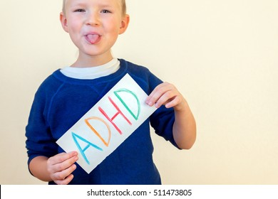 Young boy hold ADHD text written on sheet of paper and show his tongue. ADHD is Attention deficit hyperactivity disorder.