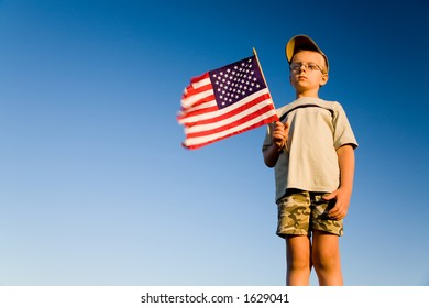 Young boy holding an American flag on a blue background of a clear sky. Space for text.