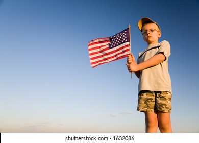 Young boy holding an American flag both hands on a blue background of a clear sky.