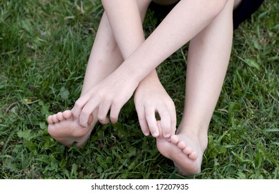 Young boy holding big/great toes with hands while sitting on grass