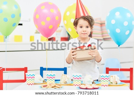 Young Boy Holding Box With Birthday Gift During Celebration In Kindergarten