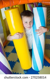 Young boy holding a colored toy columns in the children's playroom