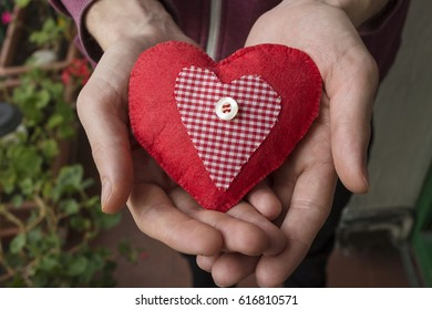 A young boy holding a fabric red heart