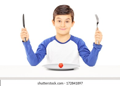 Young boy holding fork and knife with cherry tomato in front of him isolated on white background