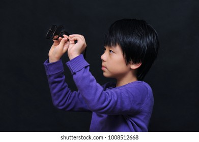 Young boy holding his glasses