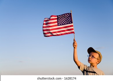 Young boy holding and looking at American flag with a clear sky background.