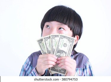 Young boy holding money on white background.