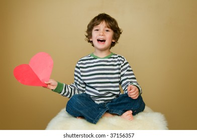 young boy holding a paper heart and laughing