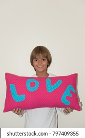 Young boy holding pink and blue decorative pillow with love written on it, smiling