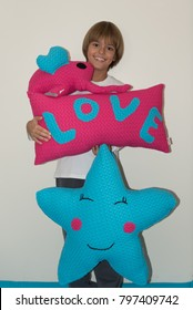 Young boy holding pink and blue decorative pillows, smiling