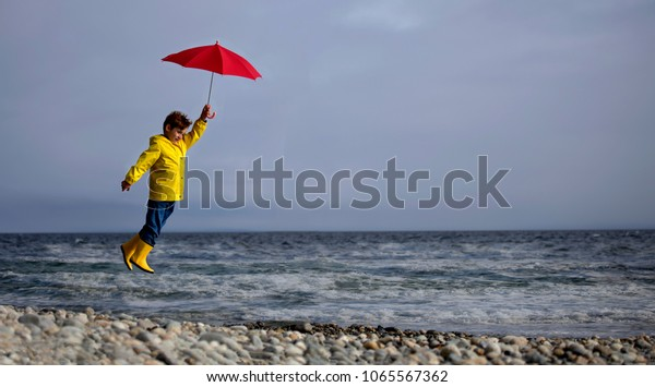 Young boy holding a red umbrella on a windy day at the ocean being blown into the air off the ground.