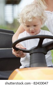 Young boy holding wheel on garden tractor