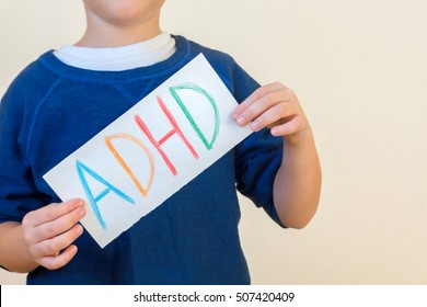 Young boy holds ADHD text written on sheet of paper. ADHD is Attention deficit hyperactivity disorder.