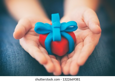 Young boy holds gift wrapped with blue ribbon. Shallow depth of field. Close up. Gift box and ribbon are made out of play clay (plasticine).