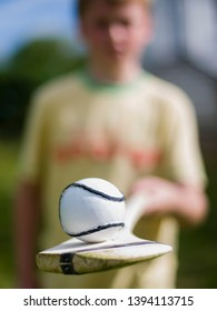 Young boy holds up a hurling stick (camán) and ball (sliotar)