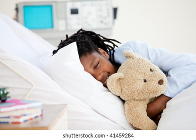 Young Boy in Hospital  hugging his teddy bear