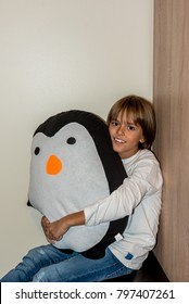 young boy hugging a favorite penguin shaped pillow, smiling at camera