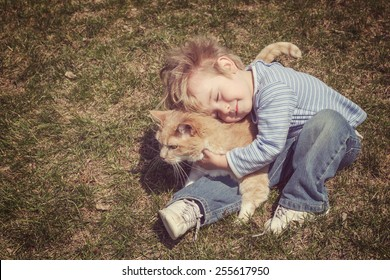 Young boy hugging his cat. Vintage instagram effect.