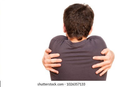 Young boy hugs himself on a white background. Rear view. His hands lie on the back. He needs to be hugged by his parents and relatives