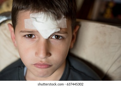 Young boy with injured forehead and bandaged wound