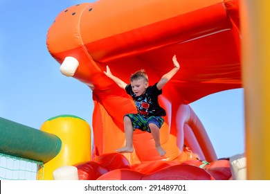 Young boy jumping barefoot on a plastic jumping castle with his arms in the air as he enjoys a summer day at a playground or fair