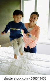 Young boy jumping on bed, mother holding his hand