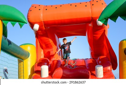 Young Boy Jumping on Bouncy Castle, Having Fun on Inflatable Slide Shaped Like Mouth of Giant Red Hippopotamus