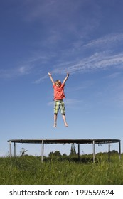 Young boy jumping on a trampoline on green meadow