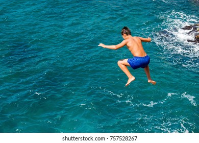 Young boy jumping in the sea from high rocks