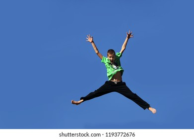 Young boy jumps for joy and propels himself into the air.  He embraces his feelings and flings his arms and legs wide.