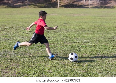 young boy kick soccer ball in green grass field, kid athlete with jersey training football in sunny outdoor park