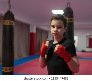 Young boy kickbox fighter in a gym with punchbags
