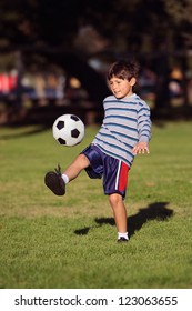 Young boy kicking a soccer ball in the park - with copy space