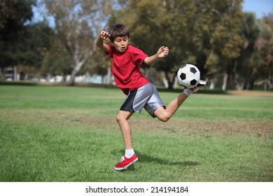Young boy kicks a soccer ball in the park - Authentic action