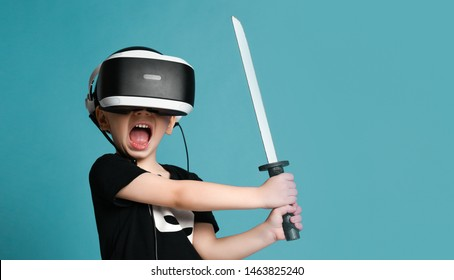 Young boy kid child play virtual reality game in vr glasses and explore alternative reality hold sword in hands. Cyber space and virtual gaming. Discover future technology on purple background banner