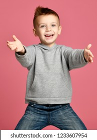 Young boy kid in grey hoodie pointing one finger at the corner smiling isolated on pink background
