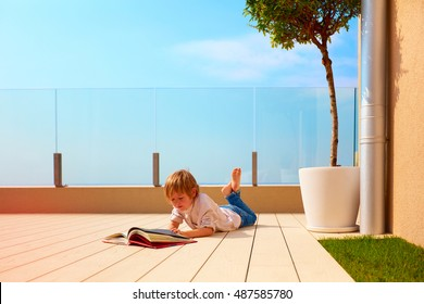 young boy, kid reading book on rooftop terrace, while lying down on decking