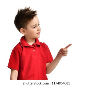 Young boy kid in red polo t-shirt pointing one finger at the corner isolated on white background