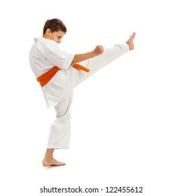 Young boy with kimono and orange belt making kick isolated on white background