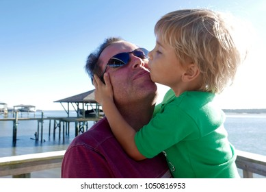 Young boy kissing his father