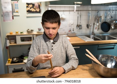 young boy in the kitchen, playing with chopsticks