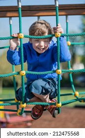Young boy laughing to camera in the park.
