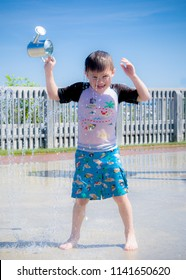 A young boy laughs as water washes over his head at a splash pad on a hot summer day in Michigan. Wearing pirate-themed swim shorts and rash guard, he holds a metal watering can over his head.