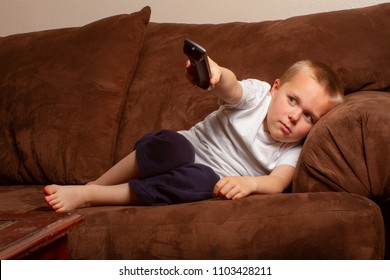 Young boy laying on the couch holding the remote and watching tv