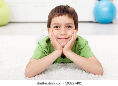 Young boy laying on the floor at home and smiling