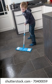 Young boy is learning how to clean a floor